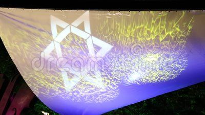 Star of David - dynamic light projection on canvas outdoor in the night.