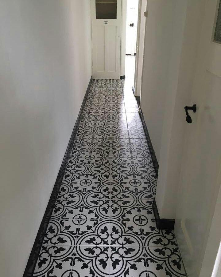 Mooie hal met een patroonvloer. Zwarte rand mooi opgelost met een hoge zwarte plint.  25x25  Tegelhuys