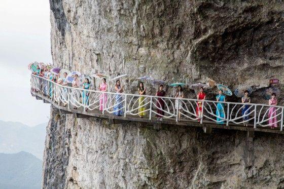 》Chongqing/China: Frauen in bunten Kleidern und Schirmen, den traditionellen Cheongsams, posieren auf einem touristischen Aussichtsweg, der in luftiger Höhe an einem Felsen entlangführt.《