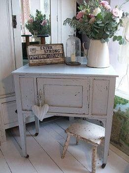 Shabby chic piece of gray furniture w/ a vignette on top