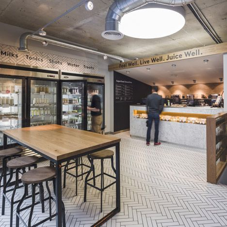 Industrial pipework runs over the ceiling of this juice bar by London office Jump Studios, featuring a ceramic herringbone floor and marble counter.