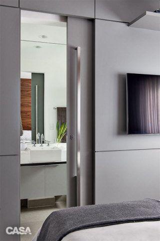 Duas soluções permitem a boa mobilidade pelo espaço – a divisória laqueada de cinza embute a porta de correr do banheiro, e a TV presa na parede dispensa a necessidade de rack ou estante. Já a paleta neutra reforça a atmosfera minimalista.