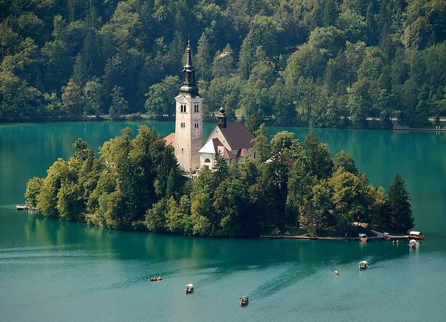 El #lago de #Bled se haya inmerso en un majestuoso entorno, flanqueado por montañas y bosques, a cincuenta y cinco kilómetros de la capital eslovena, Liubliana, cerca de la frontera con Austria. Sobre las mansas aguas del lago, se alza la única isla natural de #Eslovenia, la Isla de Bled, sobre la que se asienta una iglesia construida en el siglo XV, conocida como la Iglesia de la Asunción, siendo difícil evocar un emplazamiento más hermoso y novelesco para erigir un templo.