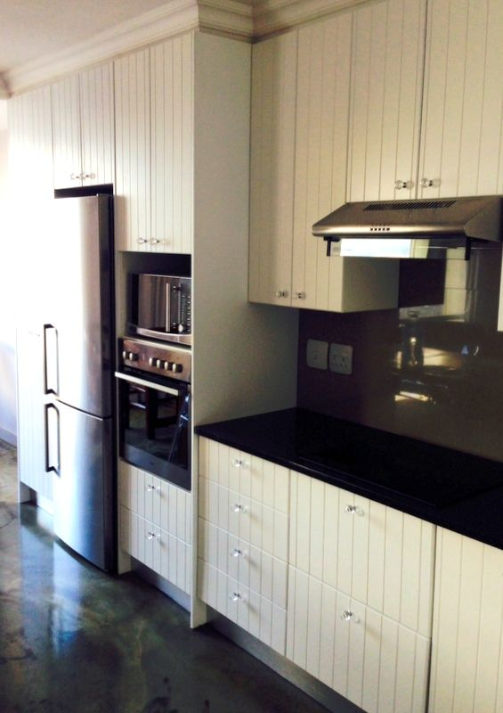 eye level ovens can be a great space saver. this kitchen is done in a farmstyle deco satin matt white