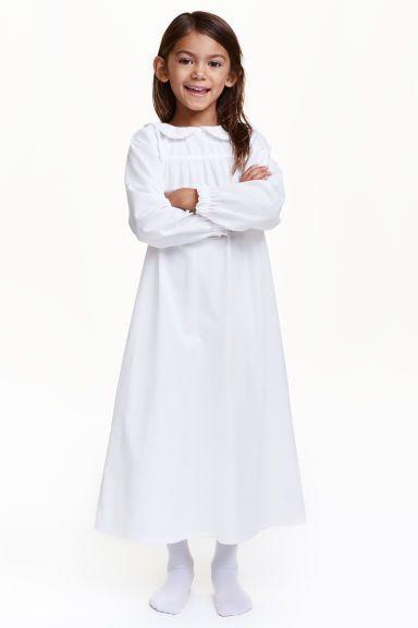 Платье Люсии: Платье Люсии из хлопковой ткани. Круглый воротник с кружевной окантовкой. Длинные рукава с небольшой оборкой и кружевным кантом снизу