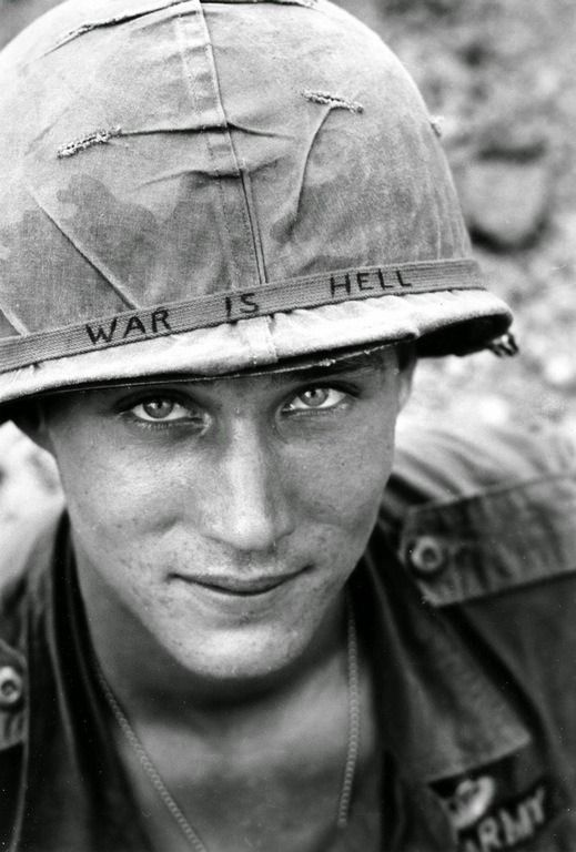"An American soldier wears a hand lettered ""War Is Hell"" slogan on his helmet • Vietnam"