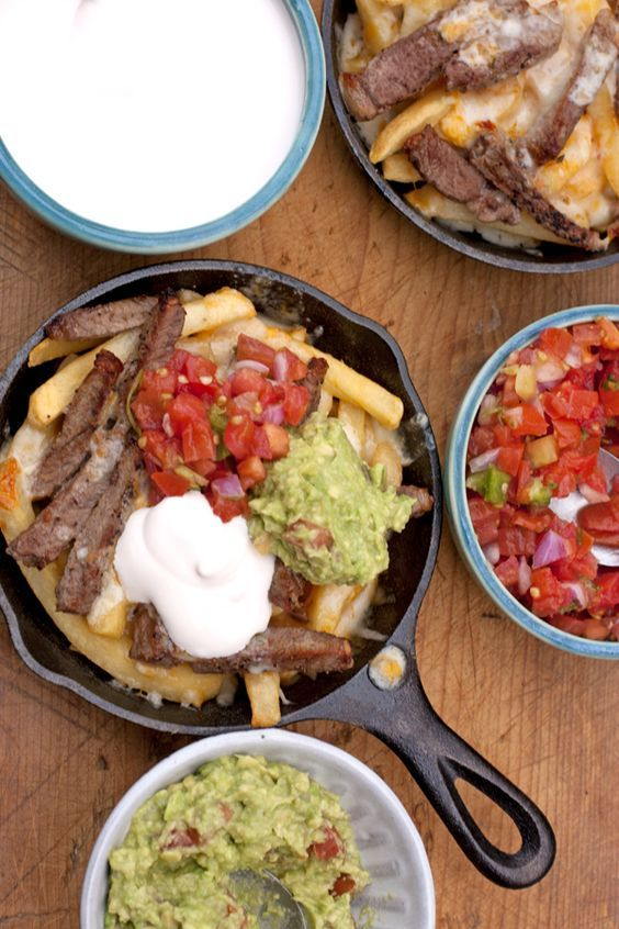 Carne Asada Fries - Muy Bueno Cookbook Freshly baked French fries, with tender pieces ofcarne asada, topped with mounds of shredded cheese, and baked till the cheese melts. Serve warm with a dollop of sour cream,guacamole, and spicypico de gallo. Talk about the perfect football food.