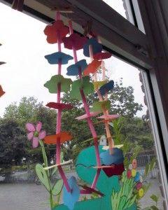 Knip stukken touw af en print bloemen uit op gekleurd papier. Laat kinderen rietjes in stukjes van ongeveer 2 cm knippen en om en om met de uitgeknipte bloemen aan het touw rijgen.