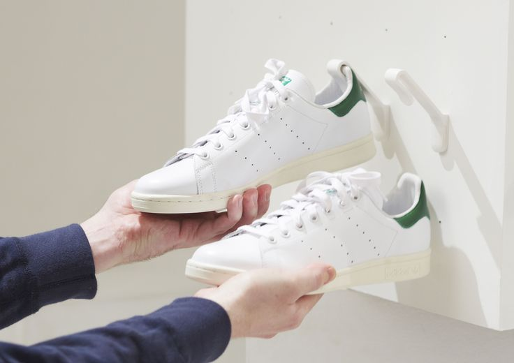 Two hands are taking a pair of white Adidas Stan Smith sneakers off of two white Staekler shoe storage hooks.