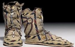 native american, America, Apache beaded hide moccasins, circa 1900, thread-sewn with heavy beadwork in colors of black, greasy yellow, rose,...