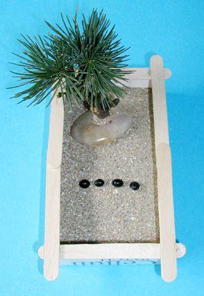 Fabriquer un petit jardin japonais - Une boîte en carton Des ciseaux De la peinture Des bâtonnets de bois ( ou des allumettes) Du sable (ou à défaut de la semoule) Un pistolet à colle ou de la colle néoprène Un arbre japonais Eventuellement un petit râteau de poupée Eventuellement quelques graines de soja