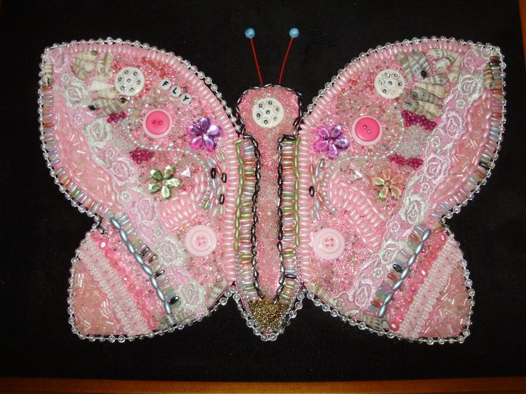 A beautiful pink butterfly made of buttons, beads, lace, braid, shells on a black material background and framed. All materials are recycled.