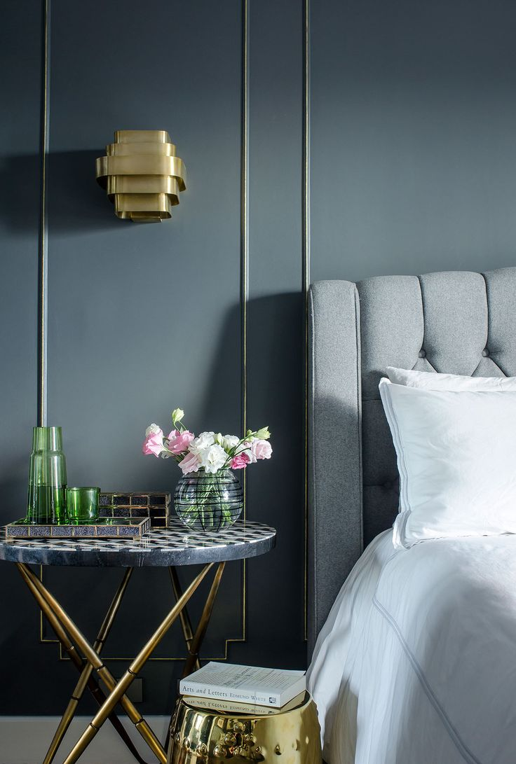 A gold bedside table and garden stool stand beside a bed upholstered in tufted gray flannel.