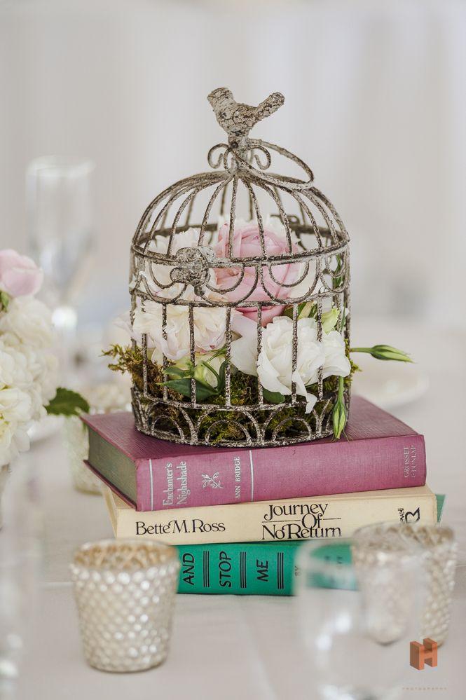 flowers in birdcage on books wedding center