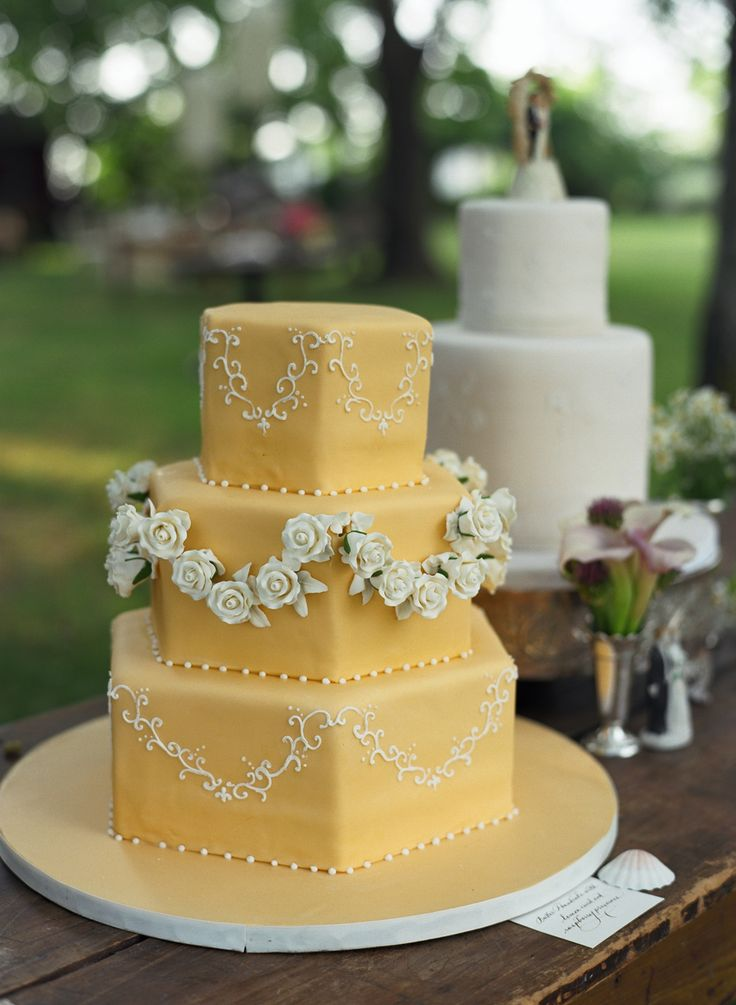 Yellow hexagonal three tier wedding cake with draped flowers and icing scalloped whimsical country rustic vintage regency Jane Austen