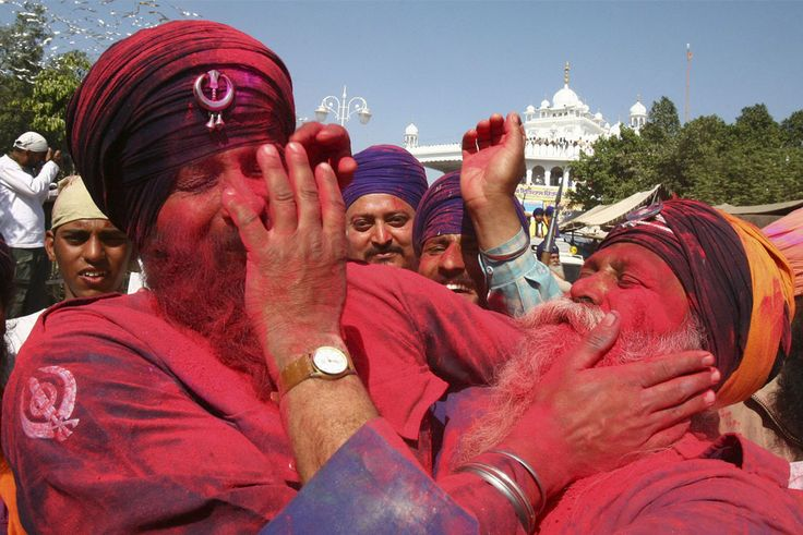 """Nihangs, or Sikh warriors, apply colored powder to each other during celebrations of """"Hola Mohalla"""" at Anandpur Sahib in the northern Indian state of Punjab"""