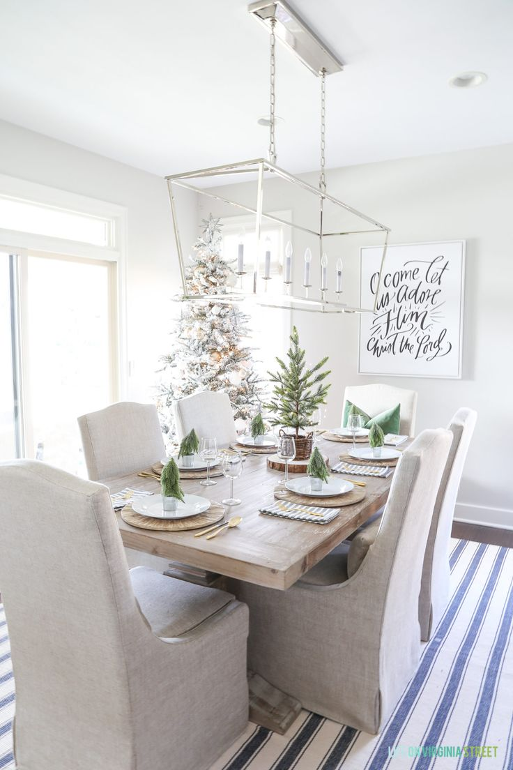 Woodland Christmas dining room with a navy blue striped rug, linen chairs, reclaimed wood dining table, 'O Come Let Us Adore Him' canvas art, and a flocked Christmas tree.