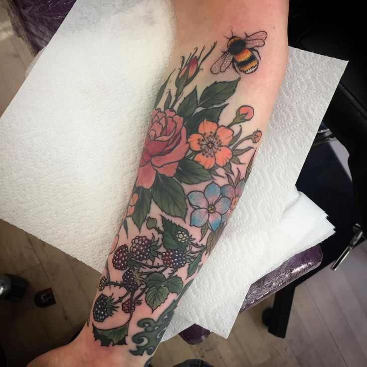 Added some blue flowers a bee and some bramble to Laura's arm that we did  last
