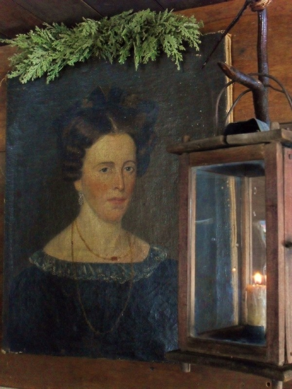 Portrait of a woman with cedar sprigs on top of frame with lantern