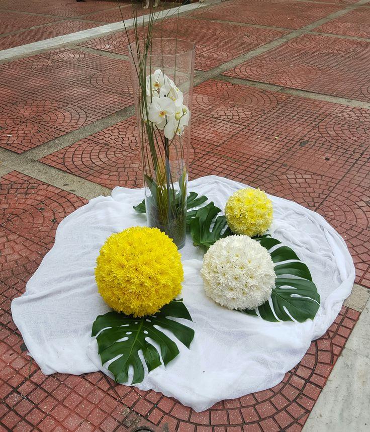 Ο στολισμός εξωτερικά στην εκκλησία έχει γίνει με μπάλες από λουλούδια σε κίτρινα και λευκά χρώματα με γυάλινο βάζο και ορχιδέα λευκή. http://www.anthemion-wedding.gr/el/stolismos-gamoy-eksoterikoi-xoroi