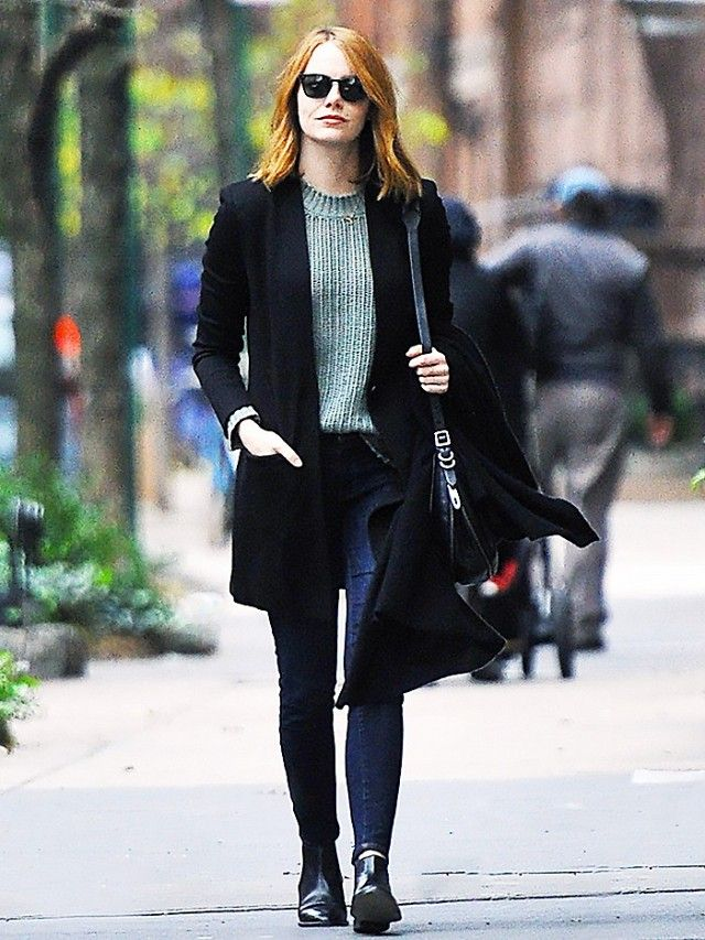 Emma Stone wears a ribbed sweater, long blazer, dark wash skinny jeans, ankle boots, a black shoulder bag, and black sunglasses