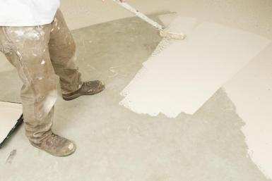 Painter Rolling Epoxy Paint on Concrete Floor - BanksPhotos/E+/Getty Images