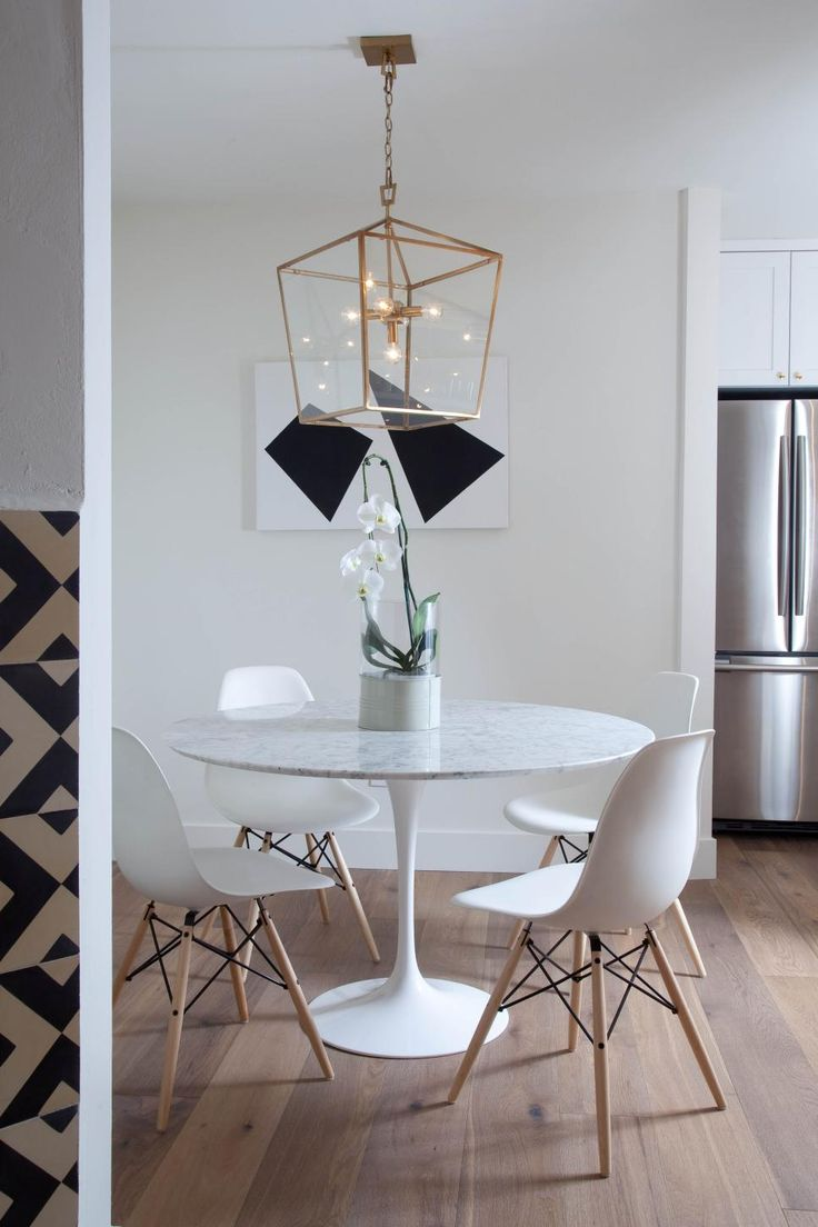White Eames-style dining chairs surround the contemporary round dining table in this minimalist dining room. Wide plank European oak wood flooring ground the space, while a chic chandelier and abstract art bring in a modern note.