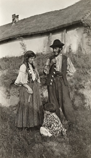 Picture Id: 949347  Gypsy parents smile and look down at their child playing in the grass. Location: Hungary.  Photographer: A. W. CUTLER /National Geographic Stock