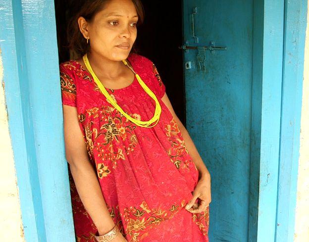 Januka stands in doorway