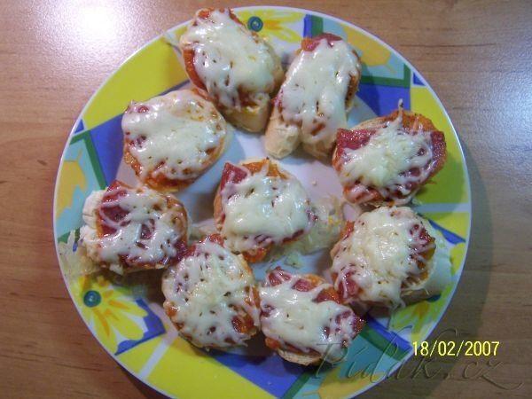 POTŘEBNÉ PŘÍSADY: rohlíky ( třebas i starší ) kečup oregano nebo koření na pizzu salám tvrdý sýr POSTUP PŘÍPRAVY: Rohlíky nakrájíme na kolečka a naskládáme na plech.