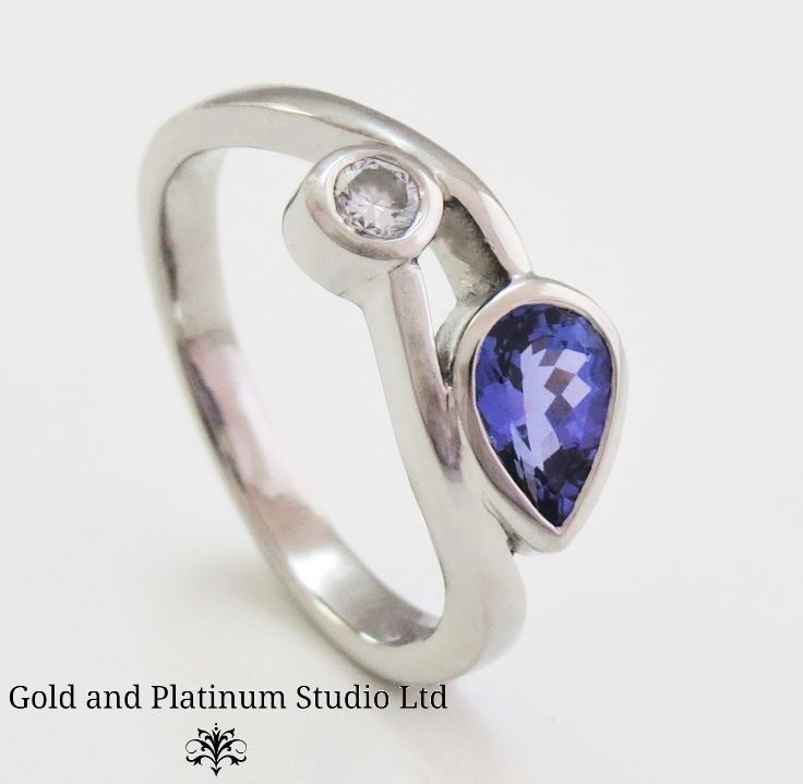 Pear shaped tanzanite hugs a round diamond, set in a crossover design.