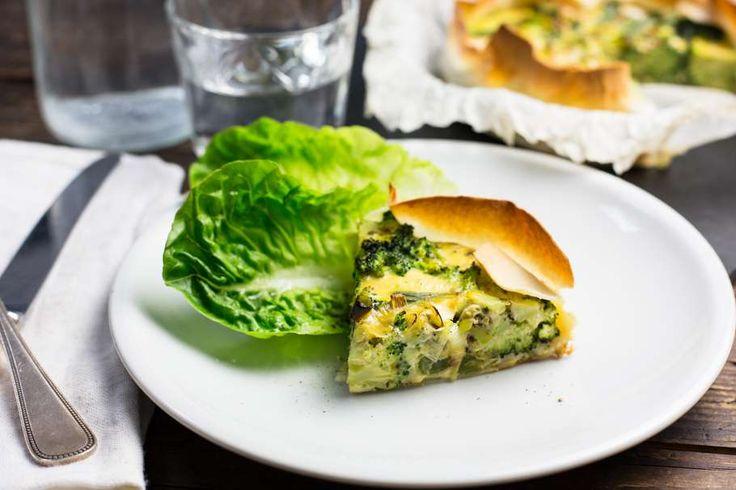 Recept voor groene groentequiche voor 4 personen. Met zout, boter, water, olijfolie, peper, prei, broccoli, knoflook, oregano, ei, crème fraîche, filodeeg, tuinerwten (diepvries) en ui