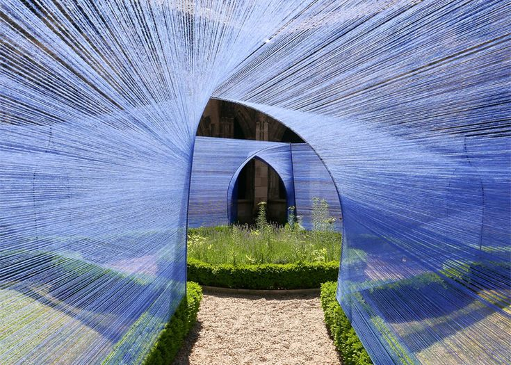 Thin blue strings are stretched between arch-shaped frames to form this installation.
