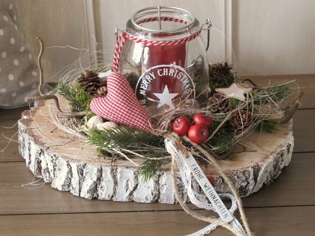 Auf einer geweißten dicken Baumscheibe wurde ein Kränzchen aus künstlichen Koniferen und Tannenzweigen, welches mit kleinen rotbackigen Äpfelchen, einem karierten Stoffherzchengeweißten Nüssen,...