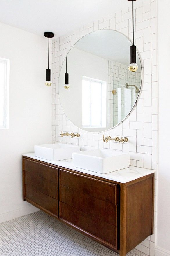 Unusual subway tile arrangement in bathroom with round mirror and pendant lights.