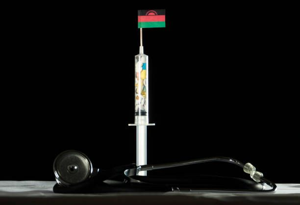 stethoscope and syringe filled with drugs injecting the malawi flag
