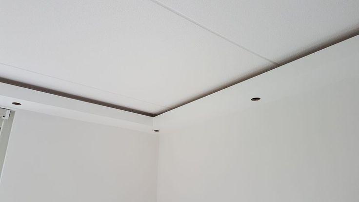 Koof gebouwd rondom de woonkamer en geverfd in hoogglans wit met ingebouwde spotjes en LED verlichting, instelbaar in verschillende kleuren.