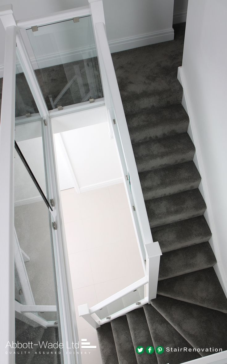 Carpeted white staircase with clamped glass balustrade