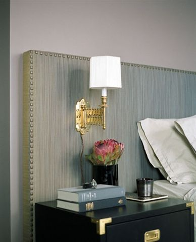 Upholstered headboard, simple clean lines of the bedside lamp.