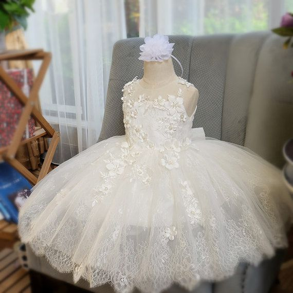 This gorgeous off-white dress is great for christening, baptism, photo prop or for any special occasions.  The bodice is accentuated with an elegant off-white lace floral trim and adorned with silk flowers decorated with rhinestone pearl center button embellishments. The back of the dress has a off-white lace bow. The bottom skirt of the dress has 1 layer of eyelash lace and 1 layer soft tulle overlay and a soft linen lining inside. It will be awesome for a flower girl at your special…