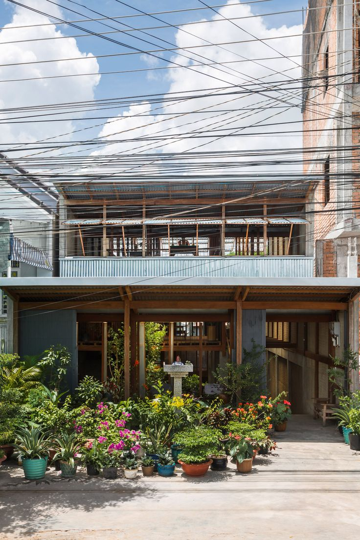"""Nishizawa Architects has replaced the facade and interior walls of this residence in Vietnam's An Giang province with moveable corrugated metal panels to create a """"half-outdoors"""" dwelling for three families."""