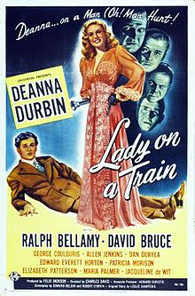 (1945) ~ Deanna Durbin, Ralph Bellamy, David Bruce. Director: Charles David. IMDB: 7.1 _____________________ http://en.wikipedia.org/wiki/Lady_on_a_Train http://www.rottentomatoes.com/m/lady_on_a_train/ http://www.tcm.com/tcmdb/title/80689/Lady-on-a-Train/ Article: http://www.tcm.com/tcmdb/title/80689/Lady-on-a-Train/articles.html http://www.allmovie.com/movie/lady-on-a-train-v98533