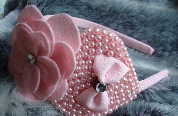 tiara forrada,  flor em feltro,  coração em pérolas rosa e  detalhes em stras R$ 30,00