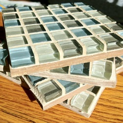 """Grout Mosaic Coasters:   1. A """"sheet"""" of moasic tile  2.Glue. Make sure to use something strong, like E6000 or something similar.  3. Square plywood- I used 4""""x4"""" squares as sheet of tile was 12""""x12.""""  4. Tile grout + tool to spread grout.  5. Sponge.  6. Felt pads."""
