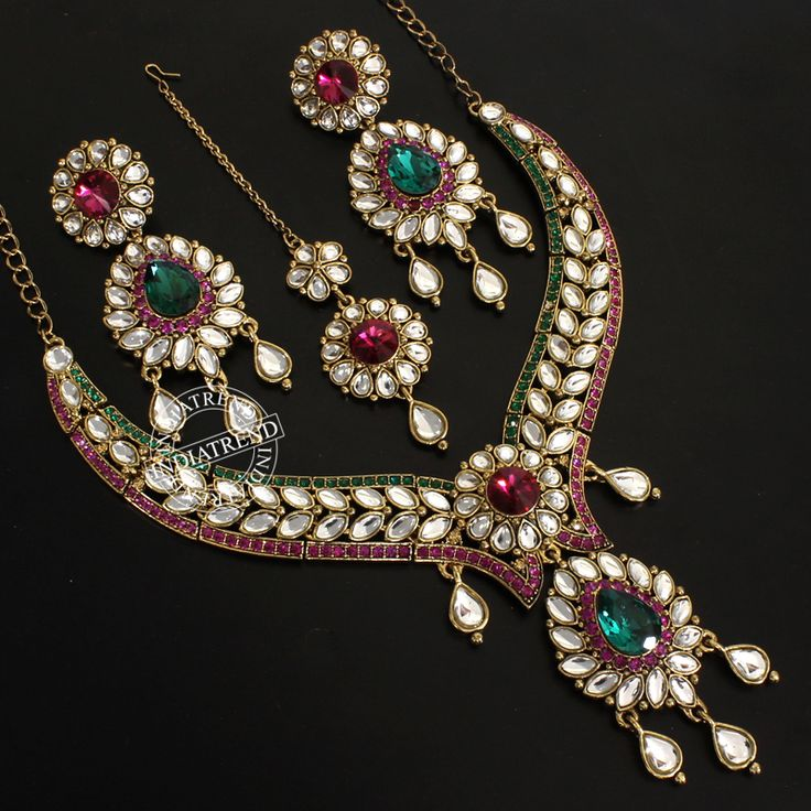 Very beautiful and Bridal Necklace set with matching dangle earrings and Maang Tikka studded with Simulated Diamonds CZs and  Simulated Pink & Green Stone.Traditional style in Gold Tone, handcrafted with high quality CZ and StoneEarrings - Measures (approx) 85mm(L) x 35mm(W) OR 3 1/2 Inch (L) x 1 1/2 Inch (W) with post back findings for pierced ears.  Necklace measures : Length (approx) - 17 1/2\\\