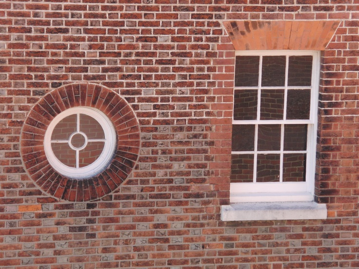 Circle and rectangle windows on a red brick wall