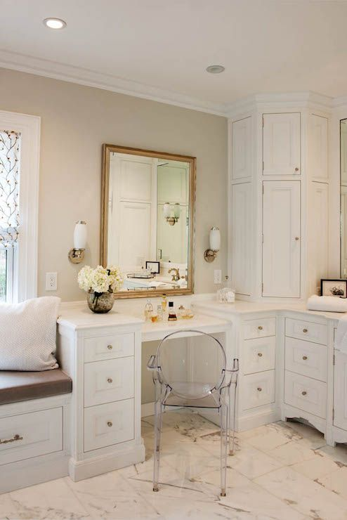 Stunning bathroom with built-in window seat to the left of a next to a drop-down vanity lined with ...