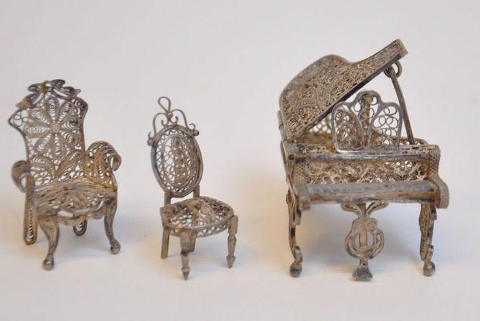 3e gehalte zilver  Een miniatuur (poppenhuis) vleugel met 2 stoelen gemaakt van filigrein zilver. De klep van de vleugen is te sluiten. De vleugel is 2.5 cm hoog (zonder bladmuziek houder) en heeft een lengte van 5 cm.