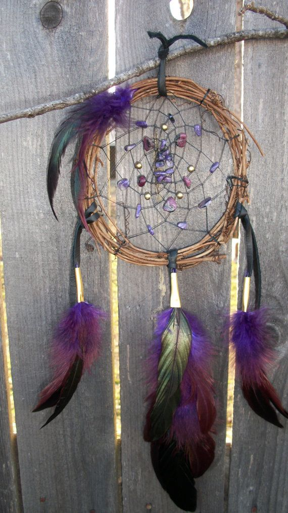 Bad dreams get caught up in the web, good dreams are clever & know how to slip through the middle. Sleep in peace with this beautiful hand-made dream catcher!    This beautiful dream catcher features semi precious stones in the web. Amethyst and brass beads with Jasper. Purple rooster feathers, Black buckskin used on the leather.