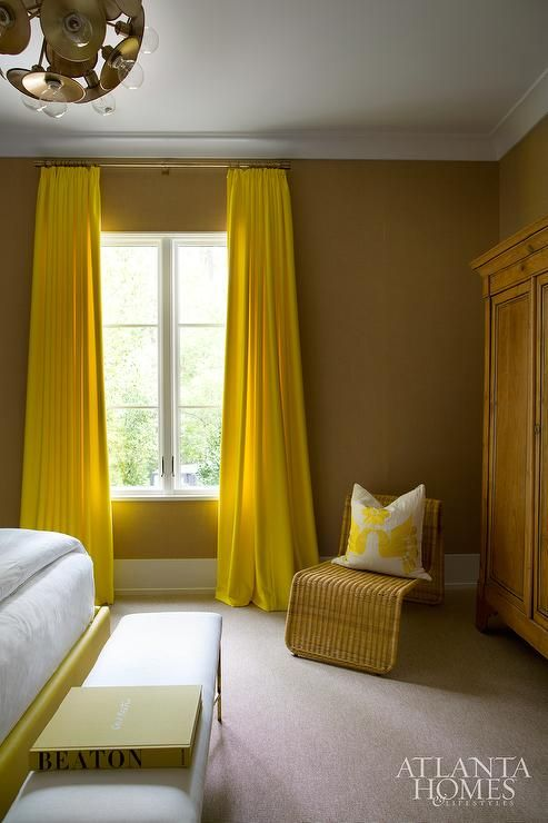 Yellow and brown bedroom features milk chocolate brown walls framing a window dressed in yellow curtains hung high next to a wicker lounge adorned with a yellow dove pillow and a wood armoire.